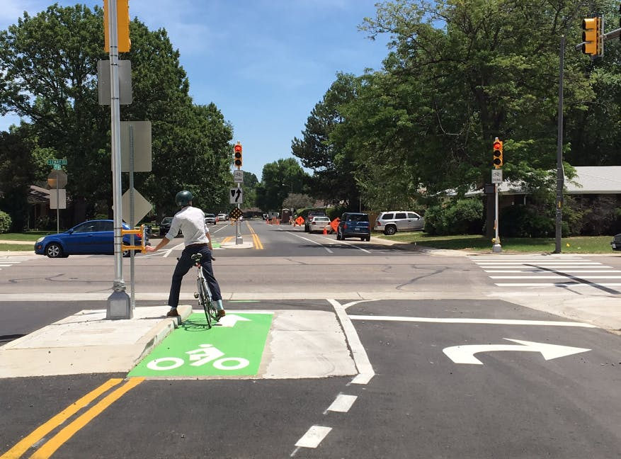 A bicyclists waits at an intersection, taking advantage of the protected bike lane.