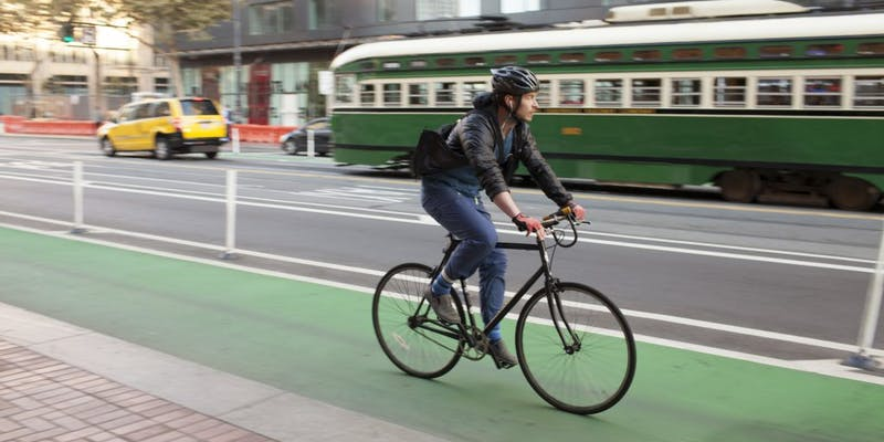 Rider in green protected bike lane