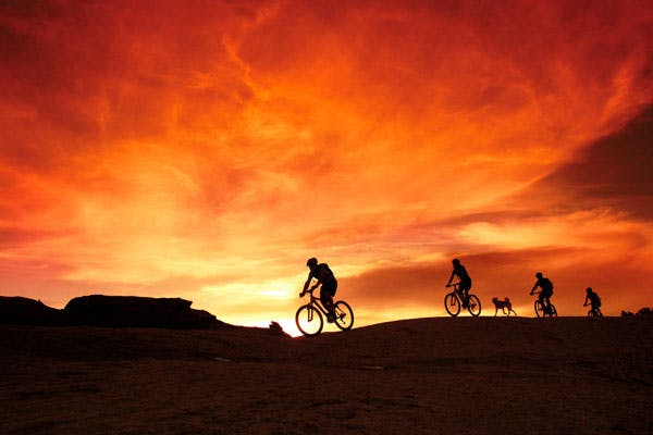 Mountain bikers against sunset