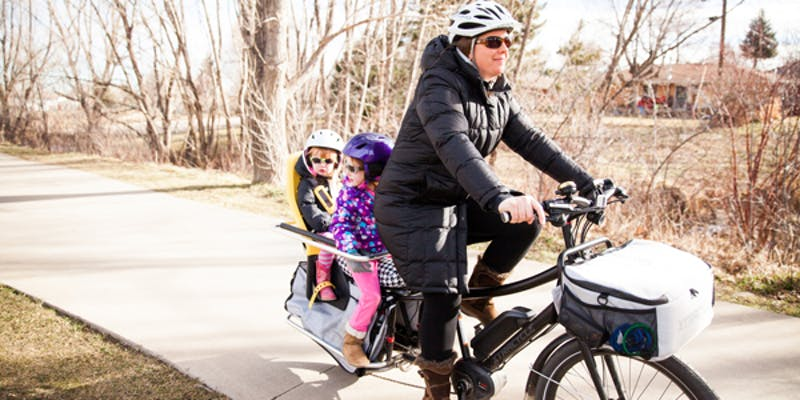 Woman on e-bike with her kids