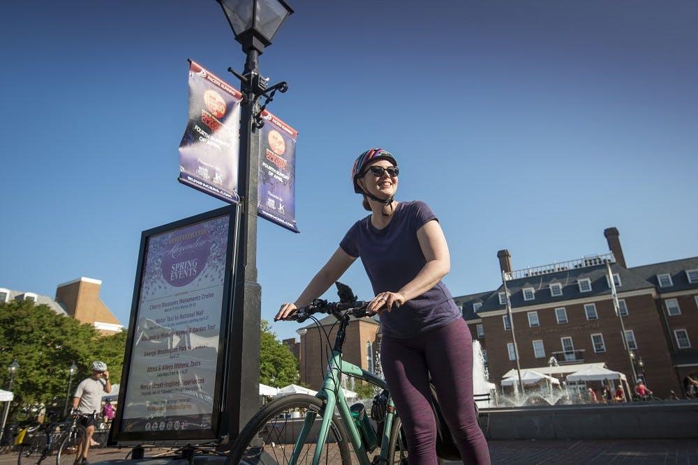 A woman walks her bike through Alexandria.