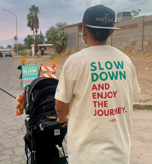 A parent walks with their child in the middle of one of Tucson's new slow streets.