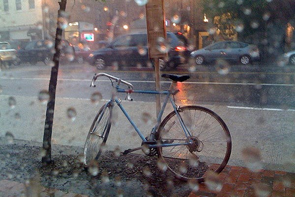 A bicycle waits in the rain.