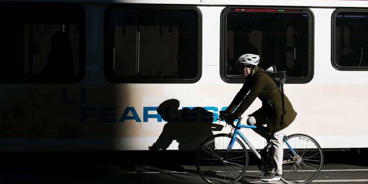 Woman biking in front of a bus, Credit: Colin Czerwinski/Unsplash
