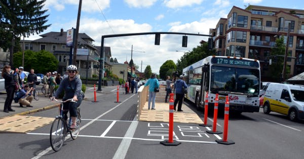 A demonstration of a floating bus stop, built from wood planks by Portland transportation advocates in 2016.
