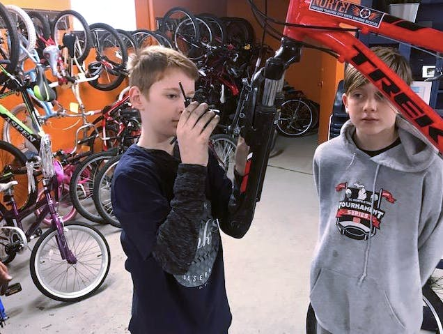 Kids learning how to fix a bike. Credit, Norte.