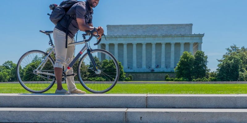 Man standing over his bicycle in front of the Lincoln Memorial