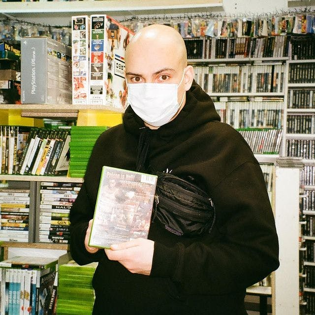 Georgi Nikolov with a mask on sitting in a retro video game shopd