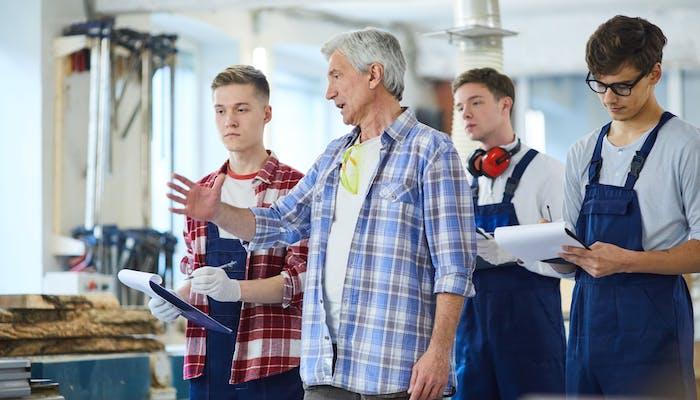 carpenter giving a tour to three interns
