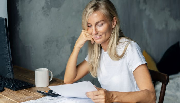 smiling woman looking at papers