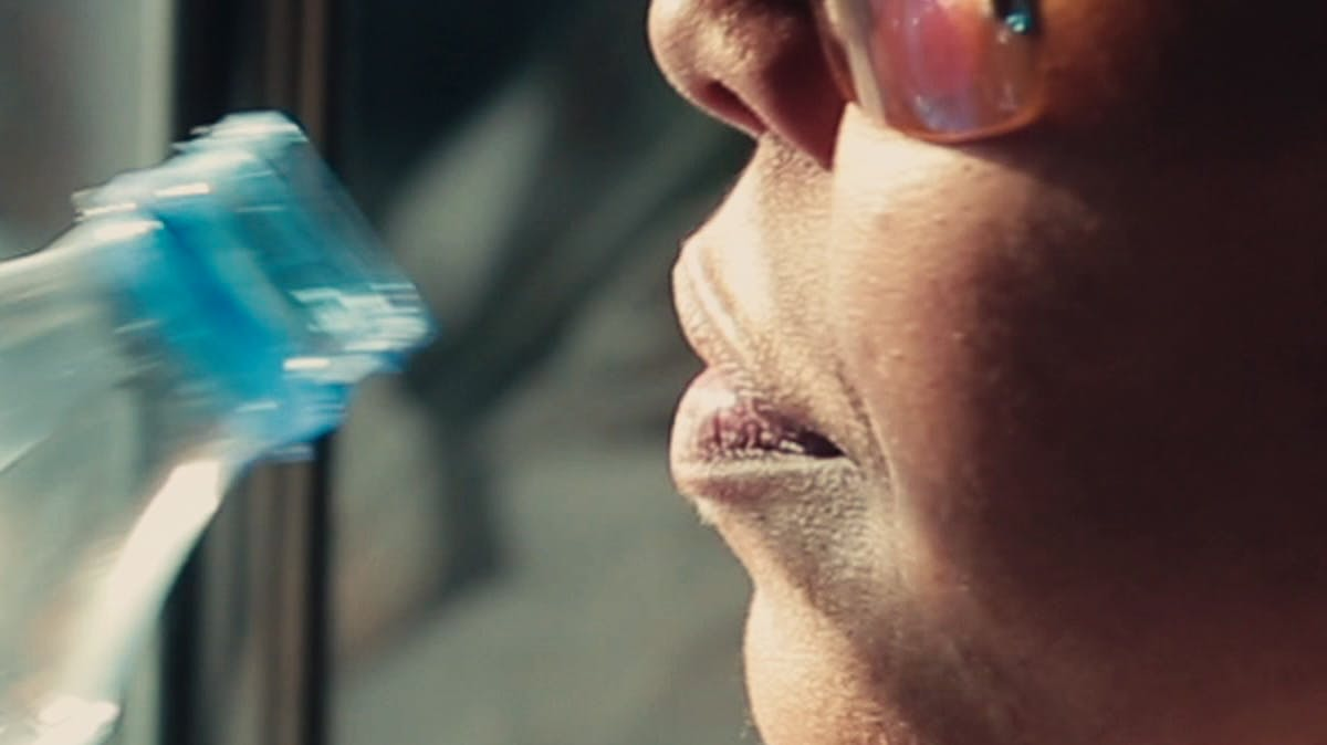 Closeup of woman drinking bottle of water