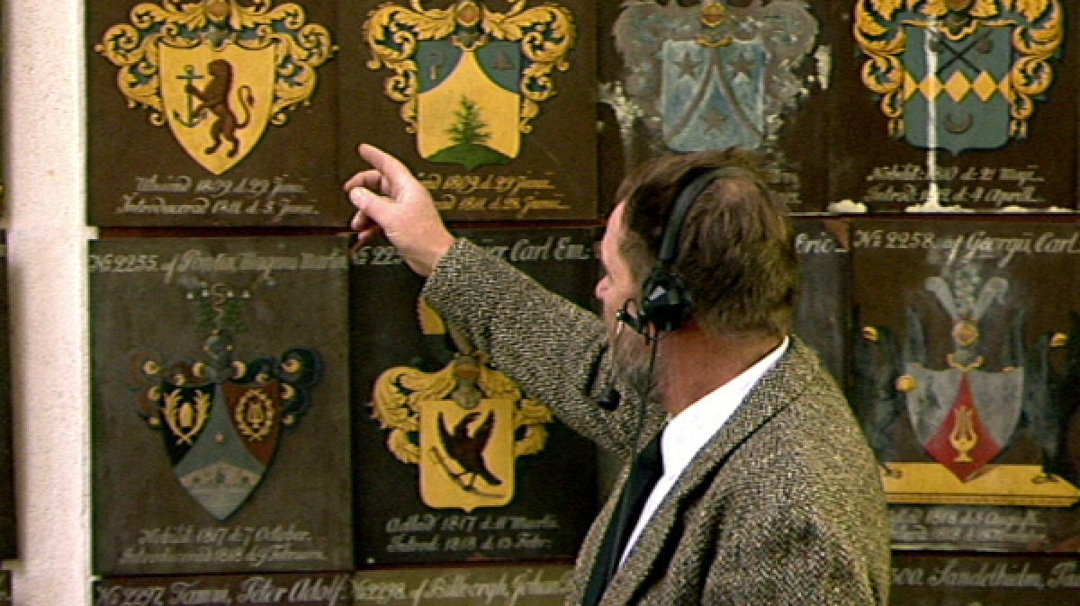 TV presenter pointing at old-fashioned crest