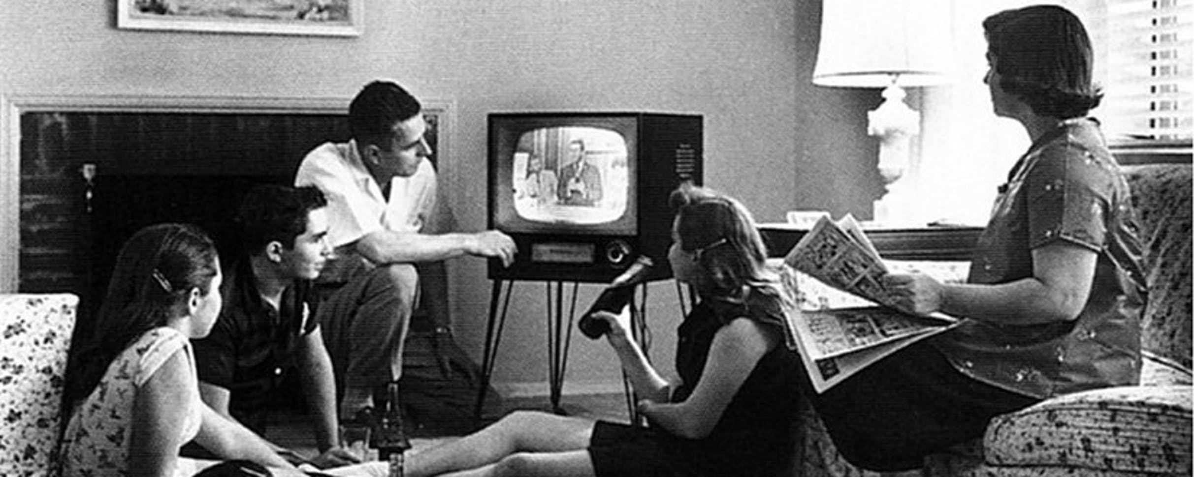 Photo of a family gathered around an old black and white television set.