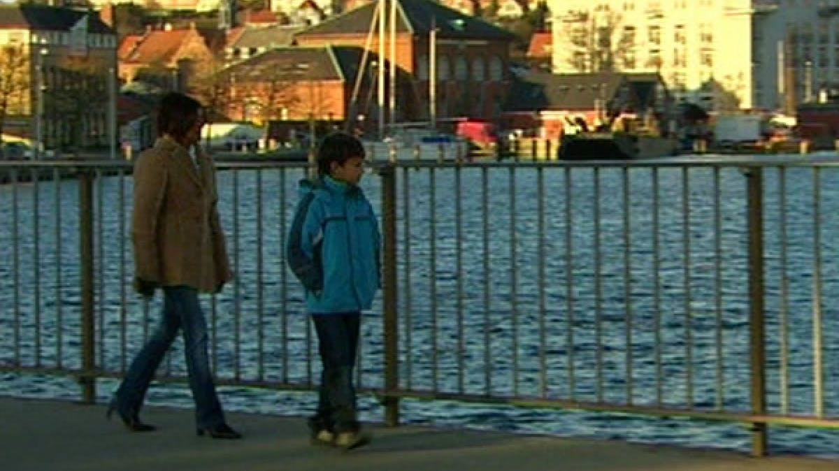 An adult and child walking up the waterfront