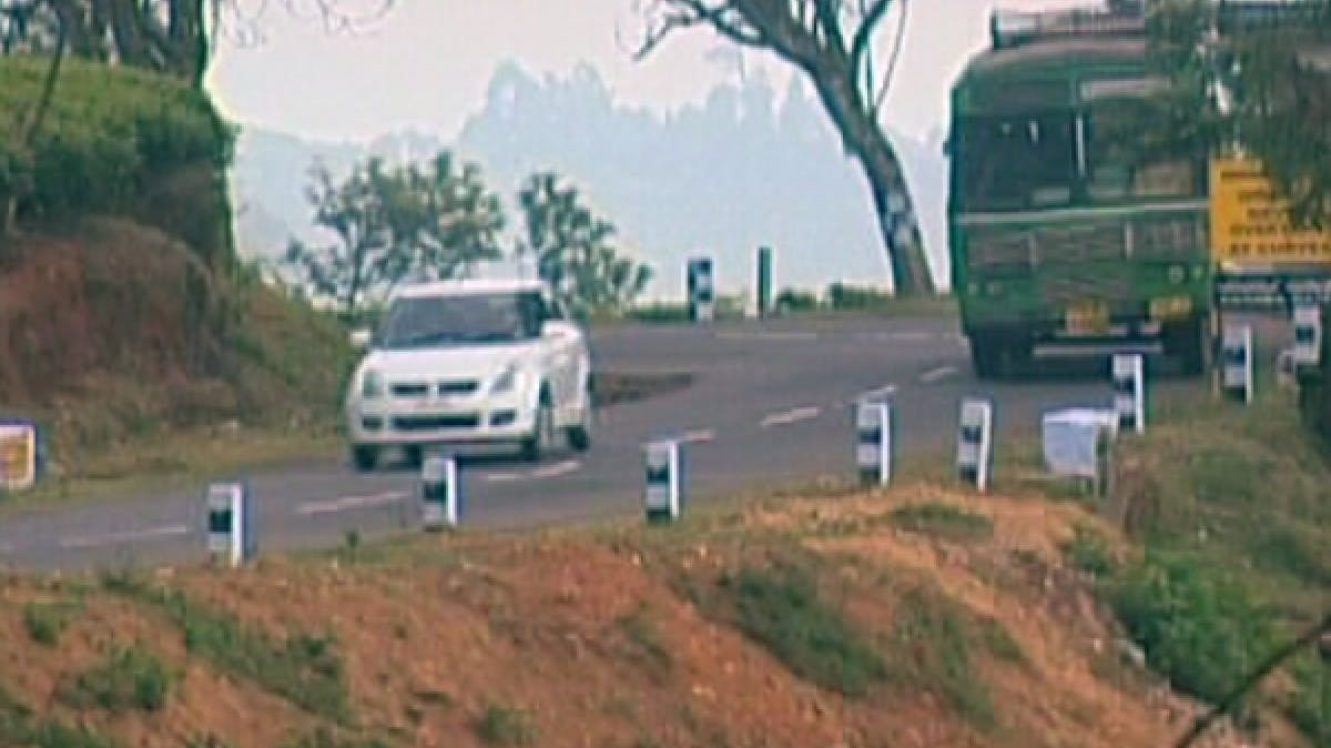 Image of white car and truck driving up winding mountain road