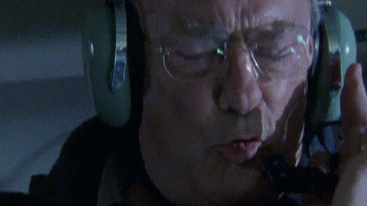 Closeup image of man's face wearing large green headphones