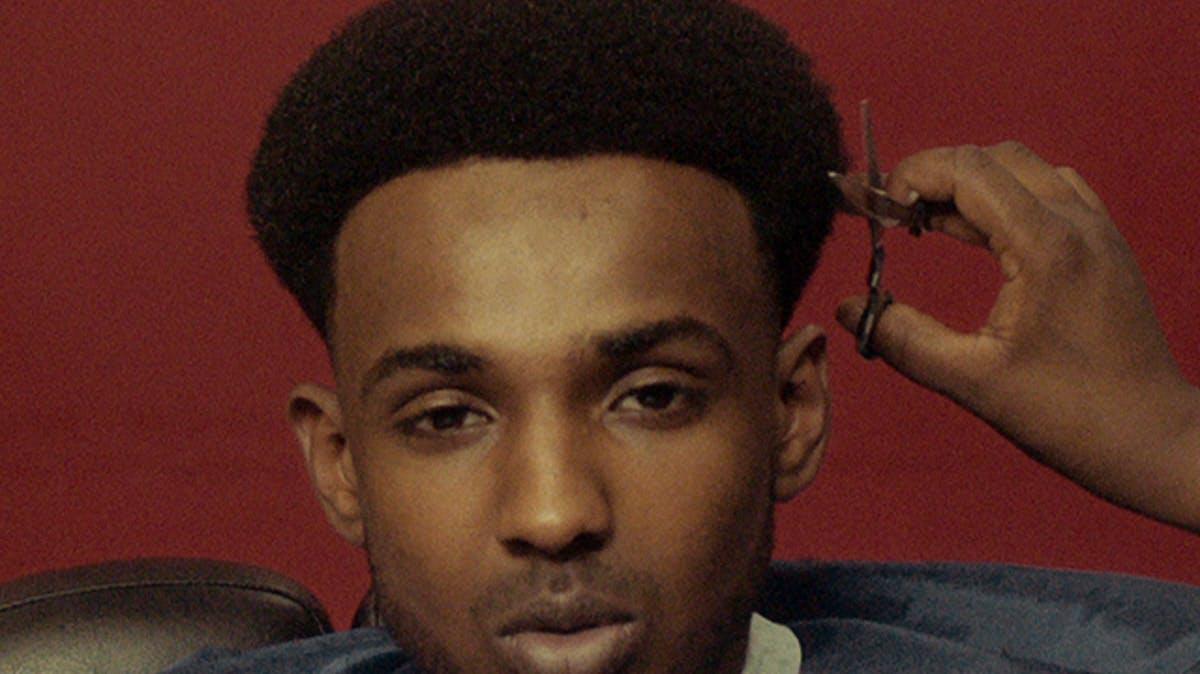Closeup of young man's face during a haircut