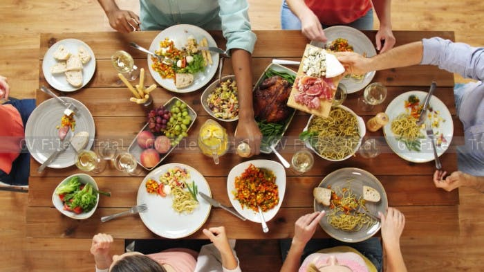 Image of dinner table with  people reaching for array of different dishes.