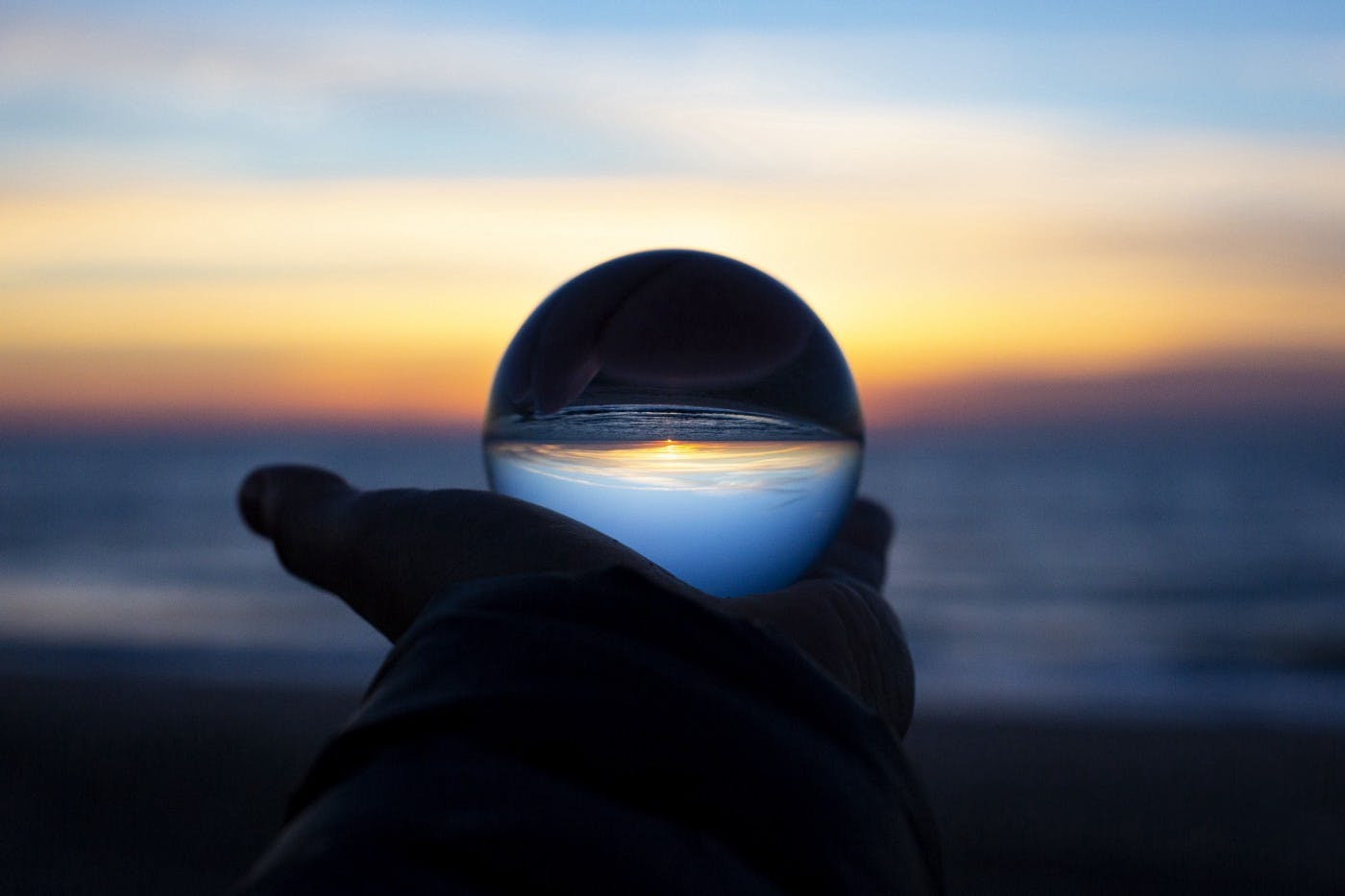 Image of a man holding out a glass ball in front of a sunset.