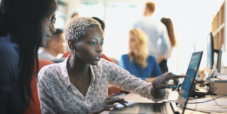 mulheres olhando conteúdo em notebook