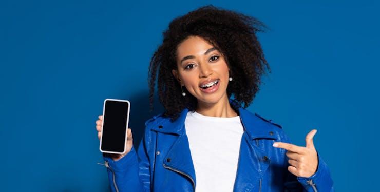Mulher apontando para o celular na mão