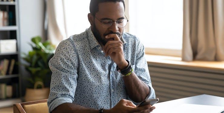 homem com dúvida olhando para celular