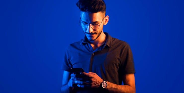 Homem olhando para celular nas mãos