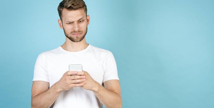 homem com duvida olhando para celular