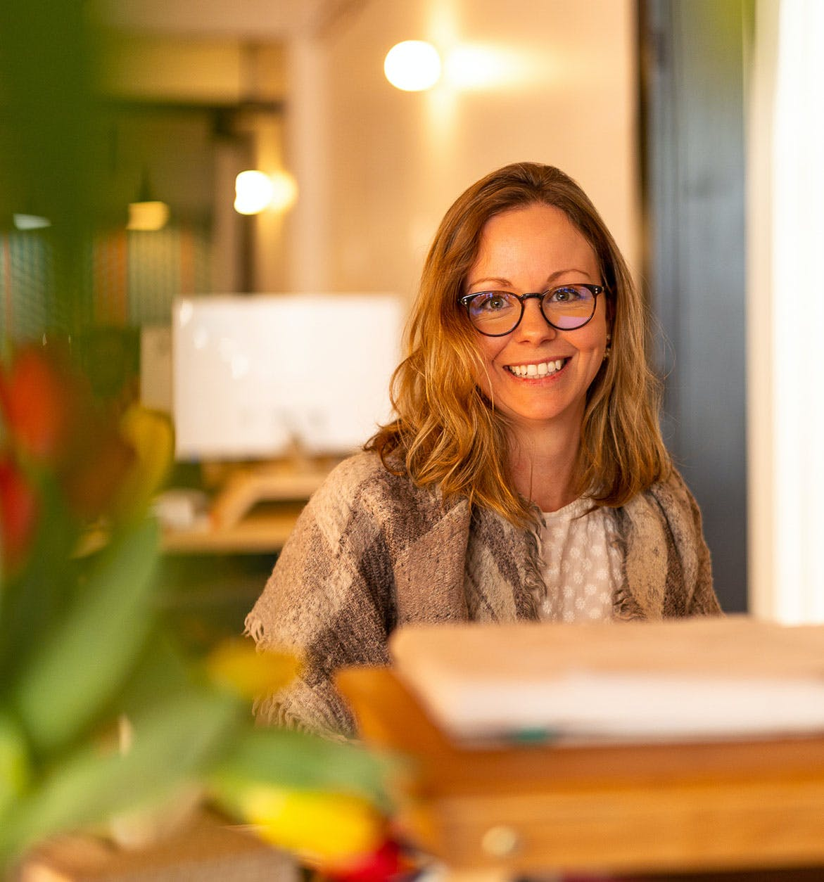 woman with glasses at plotly sitting at her desk