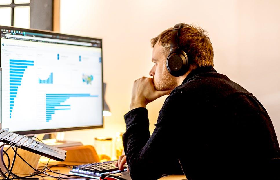 man at desk with headphones look at computer of dash enterprise