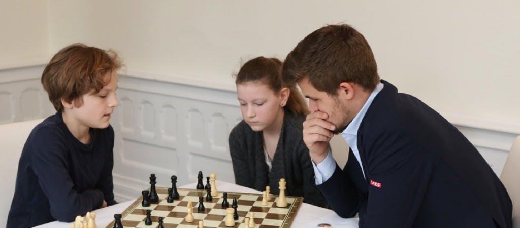 Image of Magnus Carlsen teaching two children to play Chess