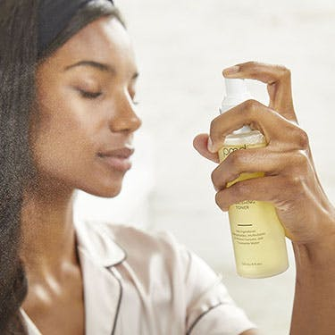 Woman spraying face with toner