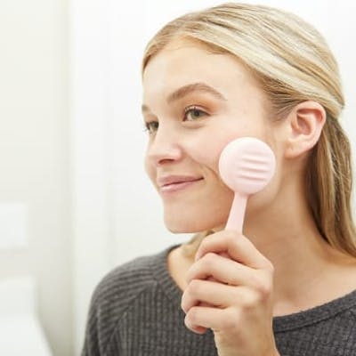 Woman washing face with PMD Clean device