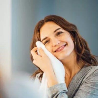 Woman patting face with white towel.