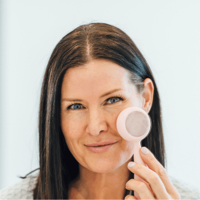 Woman washing face with PMD Clean Pro RQ