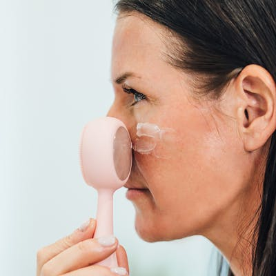 Woman applying moisturizer to face with PMD Clean Pro RQ