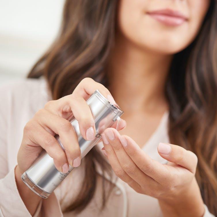 Women pouring refinish Acid Serum onto hand.
