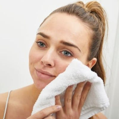 Girl patting face dry