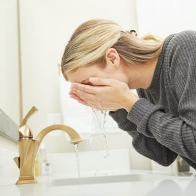 Woman rinsing her face with water
