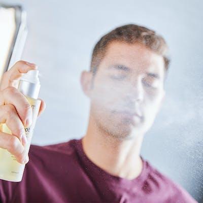 Man spraying toner on face