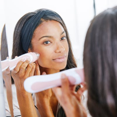 Woman staring into mirror while applying Rose Personal Microderm Elite Pro to her cheek