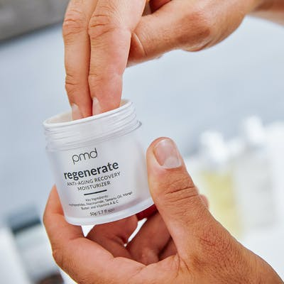 Man dipping fingers into moisturizer