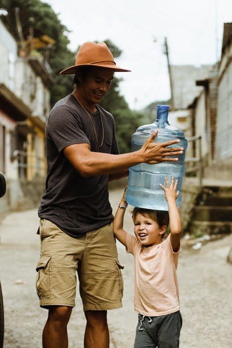 Man helping child carry a jug of water.
