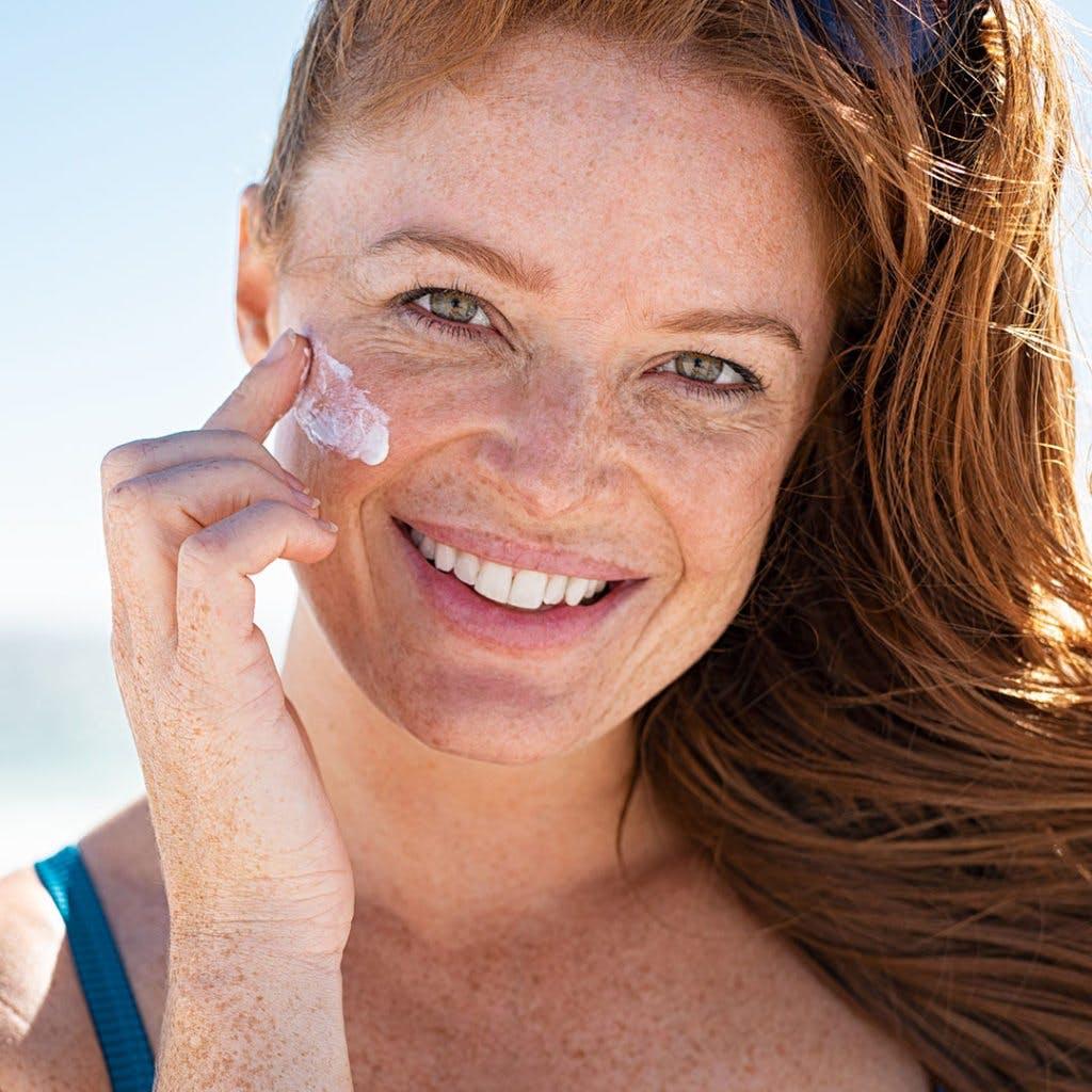 Women applying sunscreen on her face