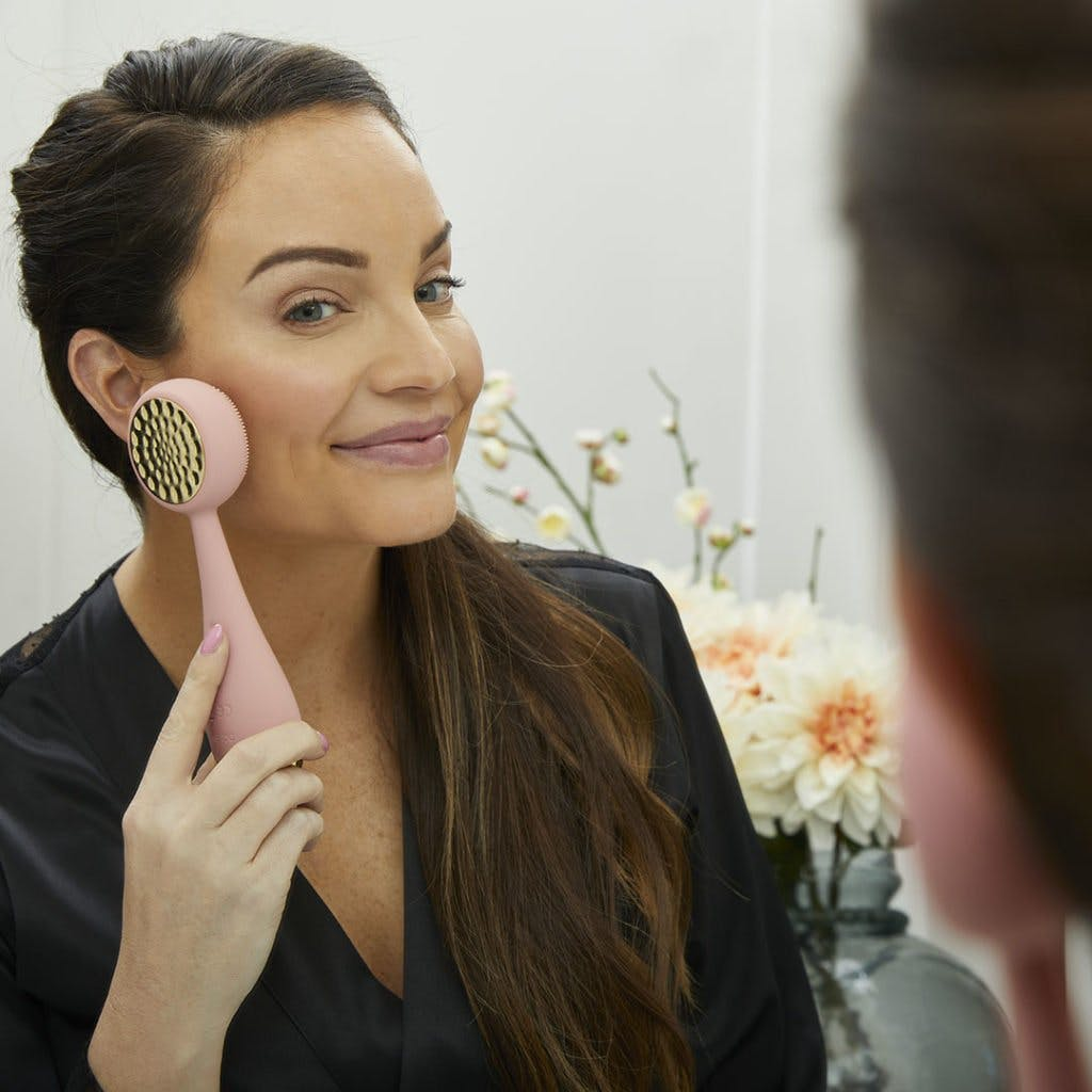 Woman using PMD Clean Pro Gold.