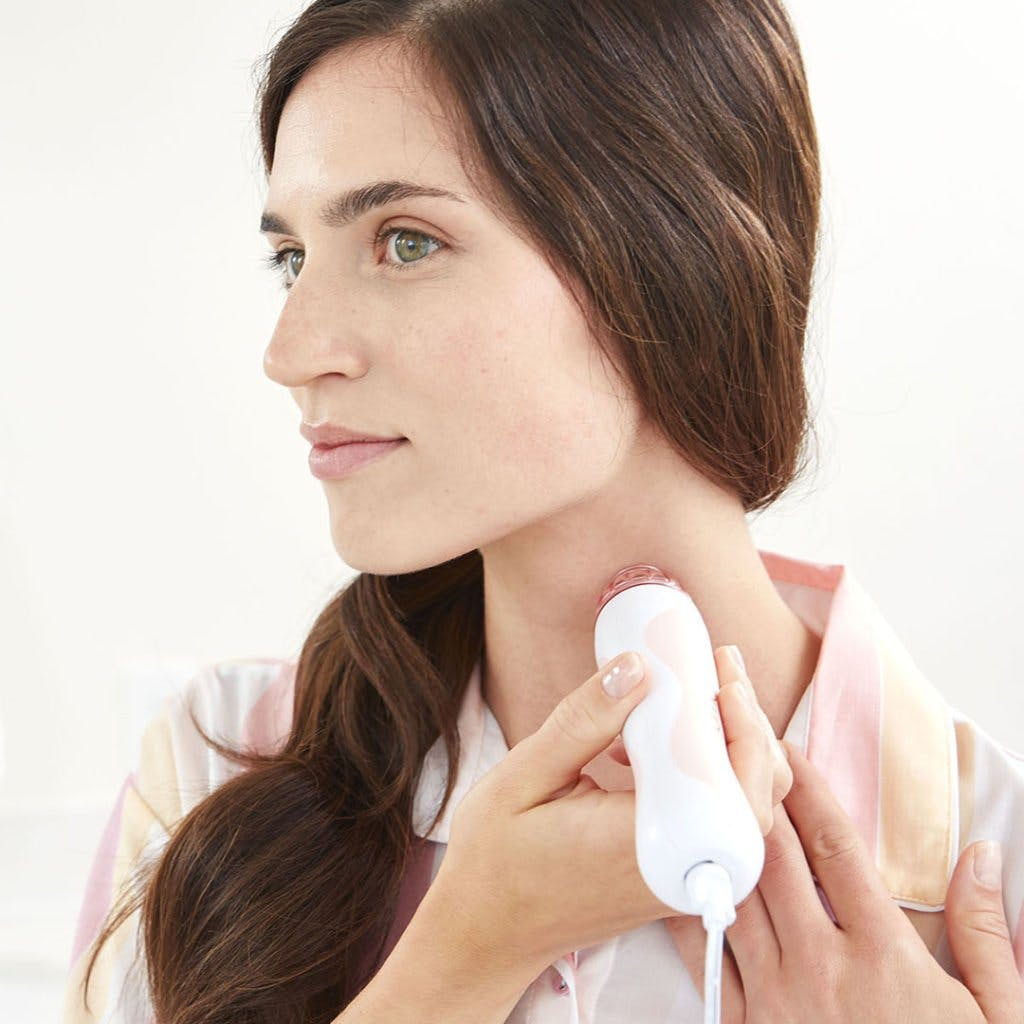 Woman using PMD using PMD Personal Microderm on neck