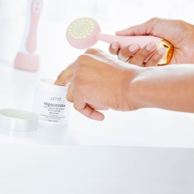 Hands applying moisturizer to device