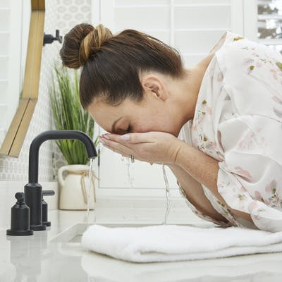 Woman rinsing face with water over a sink