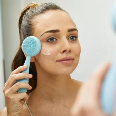Girl applying moisturizer with Sky PMD Clean Pro Silver