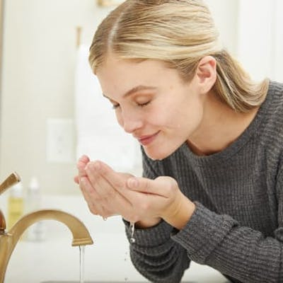 Woman rinsing her face